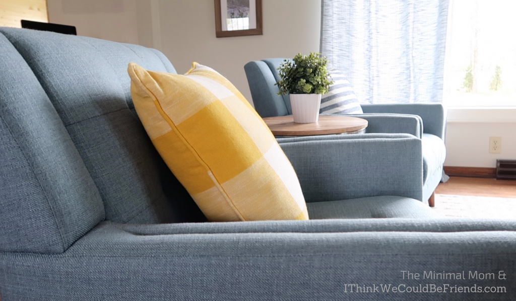 minimalist living room, blue chair, yellow throw pillow