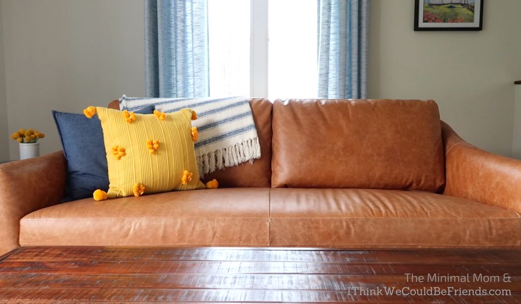 minimalist living room, brown couch, blue and yellow throw pillows